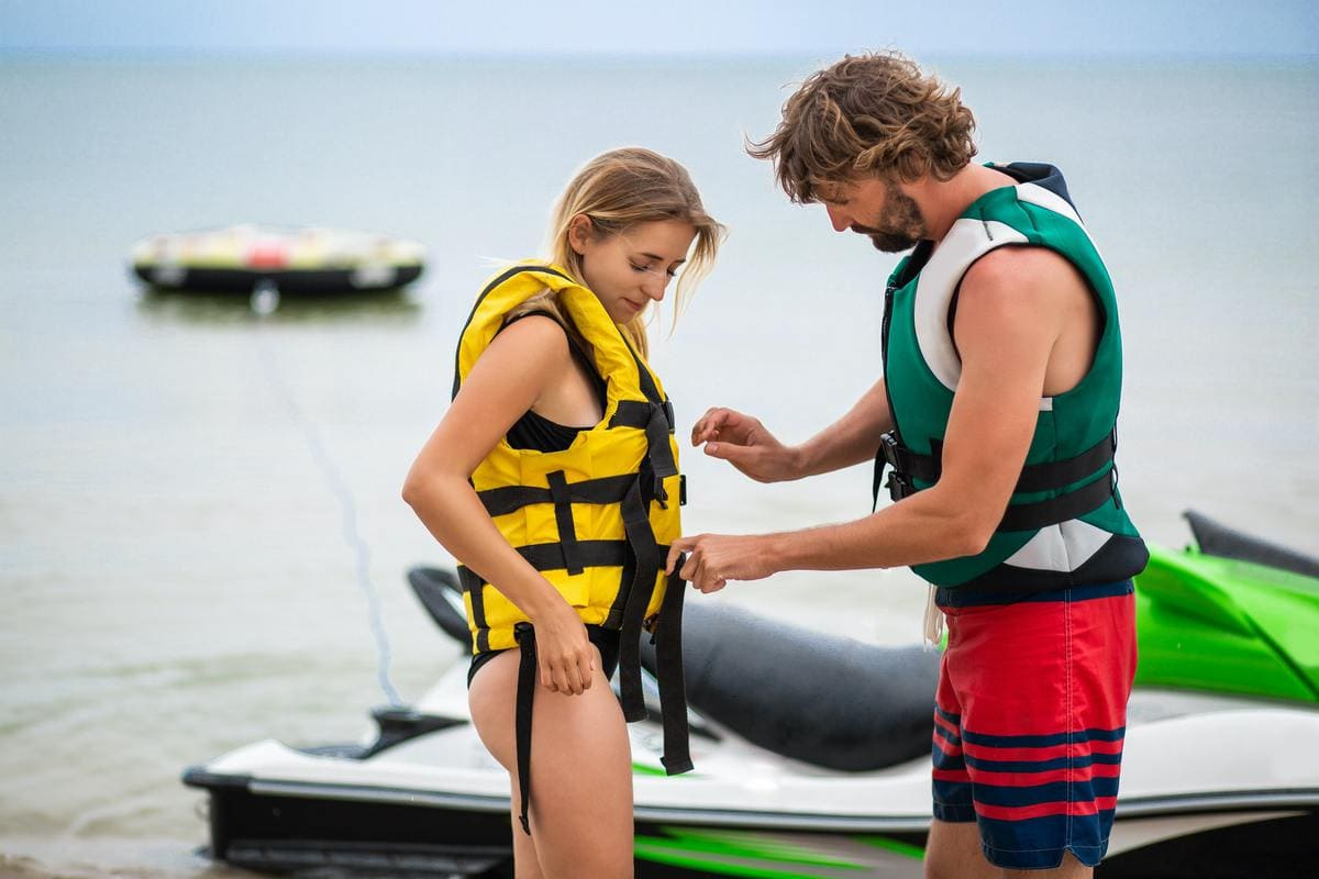 man putting life jacket on woman to ride on water scooter, summer vacation, active sport, safety